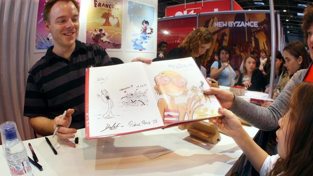 """Le dessinateur Marc Delafontaine, alias Delaf, signe un albume de """"Les nombrils"""", à côté de la scénariste Maryse Dubuc à Paris, le 15 mars 2008 [Francois Guillot / AFP/Archives]"""