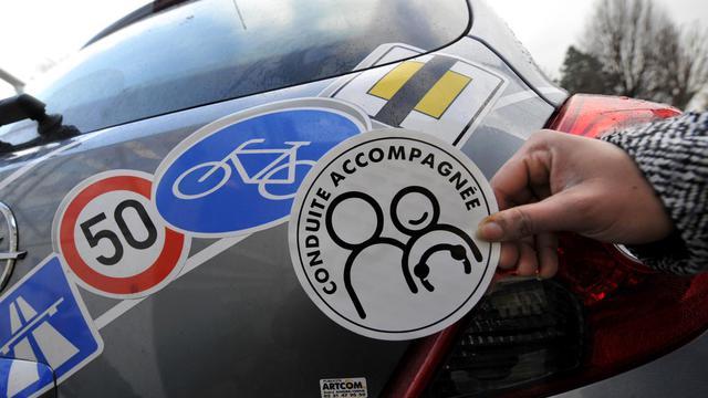 """Une personne montre, le 13 janvier 2009 à Caen, un autocollant à apposer sur le véhicule d'un jeune conducteur en """"conduite accompagnée"""". [Mychele Daniau / AFP/Archives]"""