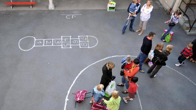 Des parents et des enfants dans une cour d'école [Mychele Daniau / AFP/Archives]
