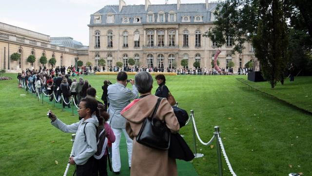 "Visitors queue up in the Elysee gardens to visit the Elysee presidential palace on September 19, 2009 at the beginning of the European Heritage Days, which take place on September 19-20. Background at right, a 2004 sculpture by Jean-Baptiste Boiteux and Nicolas Polowski : ""C'est ineluctable, il va tomber"" (Sure, it will fall down), center, a Charles Henri Fertin work, ""22032"", displayed for the event. AFP PHOTO JACQUES DEMARTHON [AFP]"