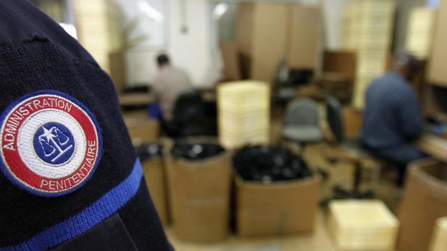 Des détenus asssemblent, sous le regard d'un surveillant, des pièces pour l'industrie automobile le 01 avril 2010 à la Maison centrale de Poissy [Joel Saget / AFP/Archives]