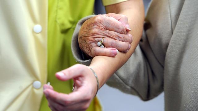 Une personne âgée marche avec une aide soignante [Jean-Francois Monier / AFP/Archives]