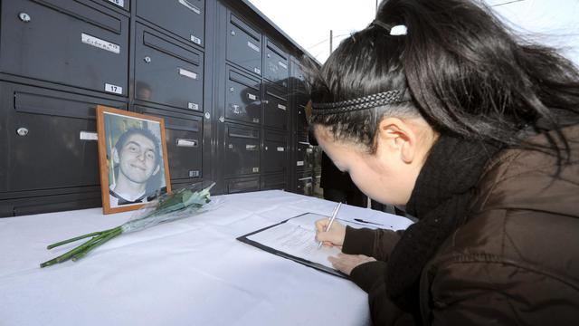 Une femme signe un registre de condoléances devant une photo de Vincent Delory, otage tué au Mali, le 16 janvier 2012 à Saint-Martin du Touch dans le sud-ouest de la France [Pascal Pavani / AFP]
