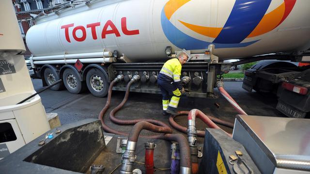 Un employé de Total livre du pétrole dans une station service [Philippe Huguen / AFP/Archives]