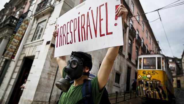 """Un homme tient un poster avec l'inscription """"irrespirable"""" le 28 may 2011, lors d'une manifestation contre l'austérité à Lisbonne, au Portugal [Patricia de Melo Moreira / AFP/Archives]"""