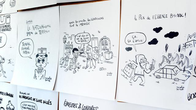 Dessins satiriques affichés sur un mur au siège de Charlie Hebdo, le 15 août 2011 [Miguel Medina / AFP/Archives]