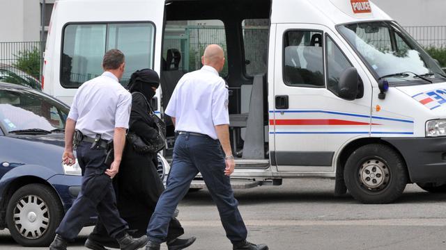 Une femme en niqab escortée par des policiers [Frank Perry / AFP/Archives]