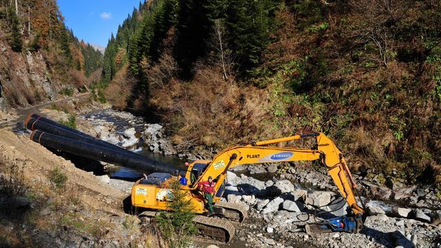 Une pelleteuse creuse dans le lit d'une rivière en Roumanie pour installer une centrale hydroélectrique, en novembre 2011 [Daniel Mihailescu / AFP/Archives]