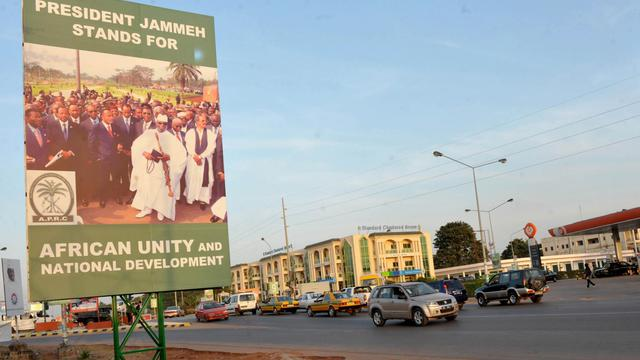 Des voitures passent devant une affiche de campagne du président Yahya Jammeh, le 22 novembre 2011 [Seyllou / AFP/Archives]
