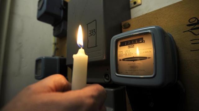 Un compteur électrique EDF éclairé par une bougie [Anne-Christine Poujoulat / AFP/Archives]