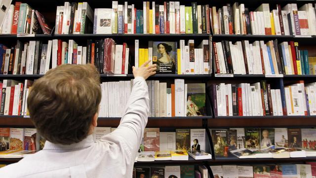 Un employé prend un livre dans une librairie [Francois Guillot / AFP]