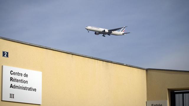 Le centre de rétention du Mesnil-Amelot, près de Paris, avec en arrière-plan un avion [Joel Saget / AFP/Archives]