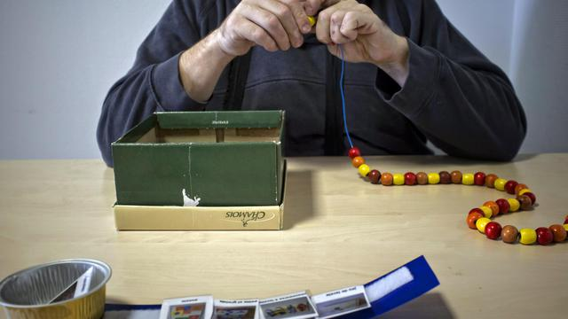 Une personnes autiste réalise un collier de perles, le 05 mars 2012 dans un centre médical à l'Isle d'Abeau. [Jean-Philippe Ksiazek / AFP/Archives]