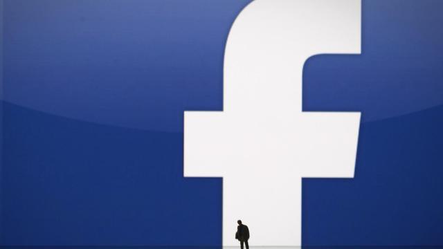 Une silhouette devant le logo Facebook [Joel Saget / AFP/Archives]