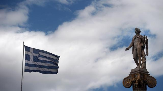 Un drapeau grec flotte à côté d'une statue antique à Athènes [Aris Messinis / AFP/Archives]