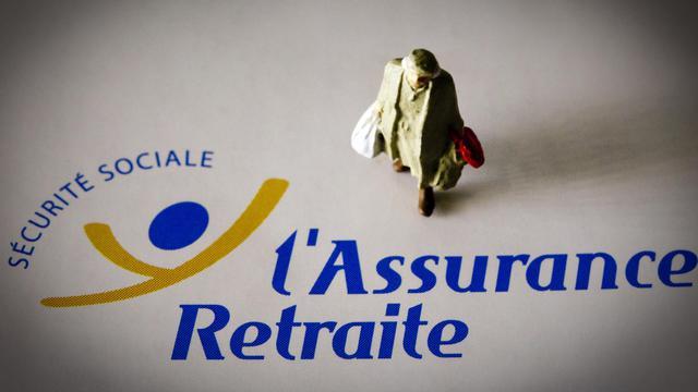 Un personnage miniature est photographié sur un document de l'assurance maladie [Joel Saget / AFP/Archives]