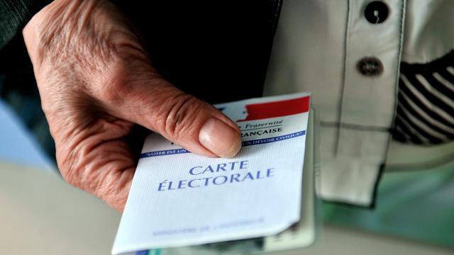 Un homme tient sa carte d'électeur [Philippe Huguen / AFP/Archives]