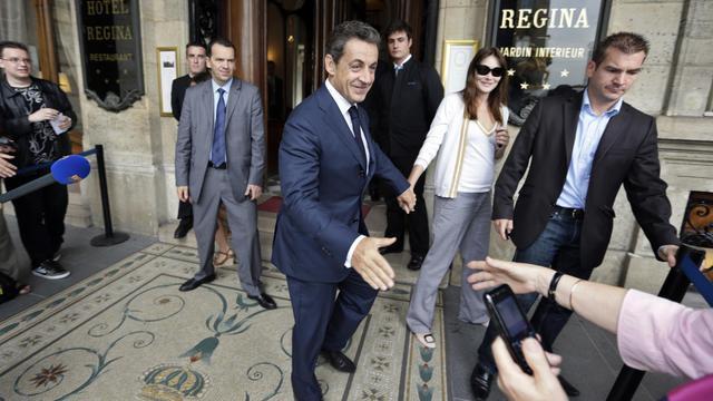 L'ex-président de la République Nicolas Sarkozy, accompagné de son épouse, Carla Bruni-Sarkozy, le 28 juin 2012, après une rencontre avec la leader de l'opposition birmane Aung San Suu Kyi, à Paris [Kenzo Tribouillard / AFP/Archives]