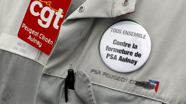 Un ouvrier de PSA porte des badges de la CGT et contre la fermeture du site d'Aulnay-sous-Bois, le 13 juillet 2012 à Paris [Thomas Samson / AFP/Archives]