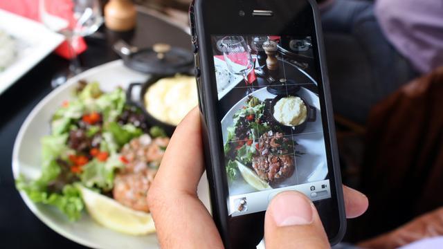 Un homme prend en photo son repas dans un restaurant, le 19 juillet 2012 à Paris [Ana Arevalo / AFP/Archives]