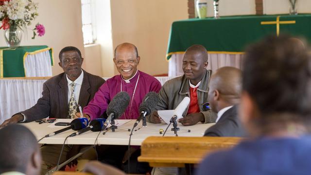 L'évêque anglican Jo Seoka (2e g) assis à côté de représentants de mineurs de la mine de platine de Marikana, en Afrique du Sud, le 28 août 2012 [Rodger Bosch / AFP/Archives]