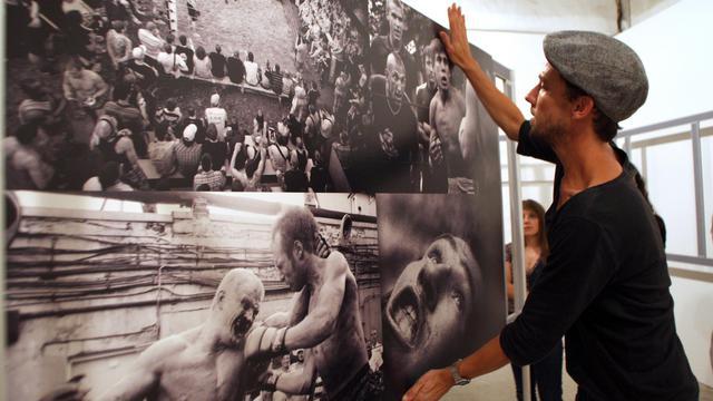 Un homme accroche une photo de Thomasz Gudzowaty avant l'ouverture du Visa pour l'Image de Perpignan le 5 septembre 2012 [Raymond Roig / AFP/Archives]