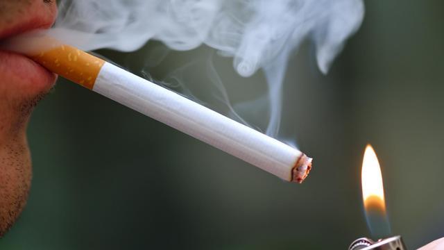 Un homme allume une cigarette [Eric Feferberg / AFP/Archives]