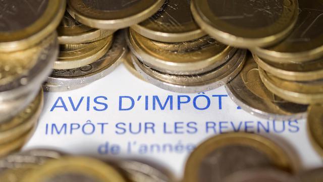 Photo réalisée en 2012 d'un avis d'imposition sur le revenu recouvert de pièces en euros [Joel Saget / AFP/Archives]