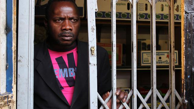 Michel Nhema Bahati, immigré congolais, se tient derrière la grille de sa boutique, le 4 septembre 2012 à Yeoville [Cynthia Matonhodze / AFP]