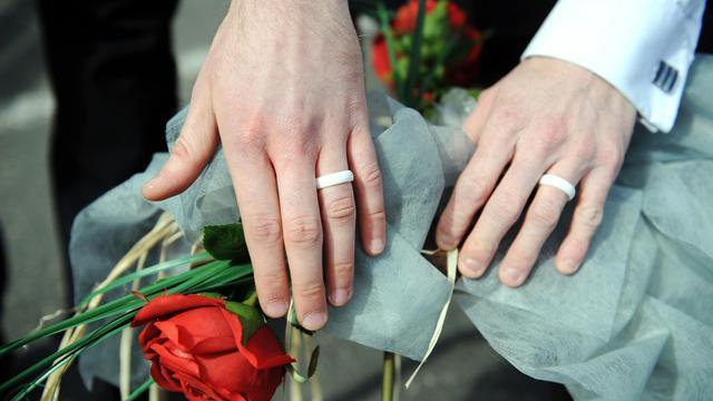 Les mains de deux homosexuels portant des alliances lors de la célébration symbolique de leur mariage [Fred Tanneau / AFP/Archives]