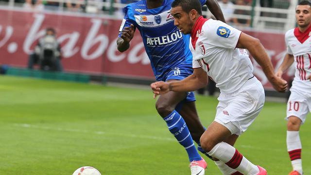 L'attaquant de Lille Dimitri Payet (blanc) conduit son ballon sous les yeux du Franco-Congolais Granddi Ngoyi (bleu), lors du match de L1 contre Troyes, le 15 septembre 2012 [Francois Nascimbeni / AFP/Archives]