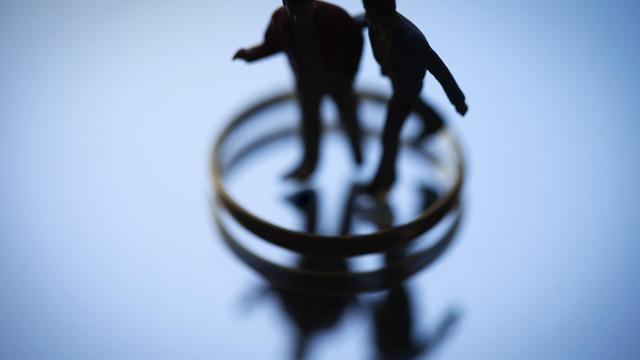 Deux figurines entourées d'alliances [Joel Saget / AFP/Archives]