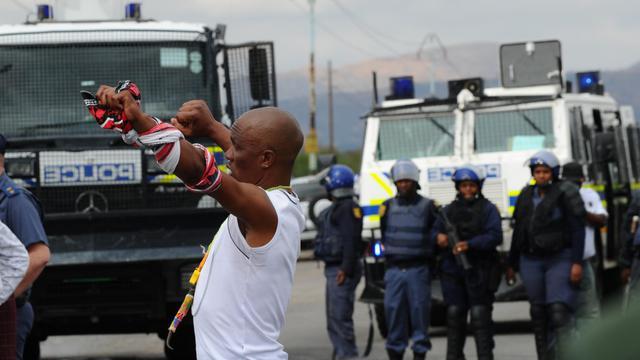 Un mineur face à des policiers déployés le 16 septembre 2012 à Rustenburg [Alexander Joe / AFP]
