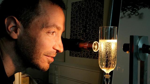 le physicien Gérard Liger-Belair observe une flûte de champagne, le 13 septembre 2012 dans son laboratoire de Reims [Francois Nascimbeni / AFP]