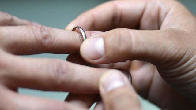 Un homme passe une alliance au doigt d'un autre [Kenzo Tribouillard / AFP/Archives]