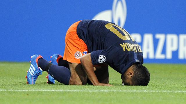 L'attaquant marocain de Montpellier Younes Belhanda embrasse la pelouse après avoir marqué un penalty contre Arsenal en C1, le 18 septembre 2012 [Pascal Guyot / AFP]