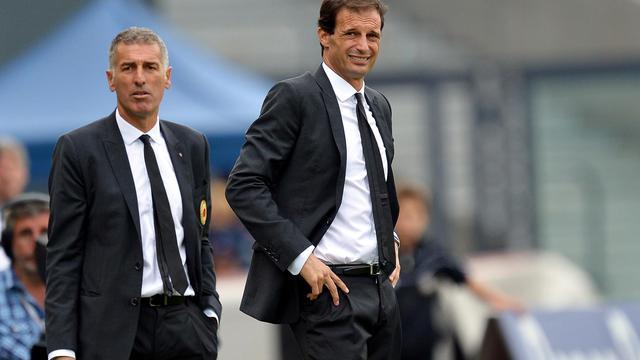L'entraîneur de l'AC Milan Massimiliano Allegri grimace, aux côtés de son adjoint Mauro Tassotti, lors du match contre l'Udinese, le 23 septembre à Udine. [Vincenzo Pinto / AFP]