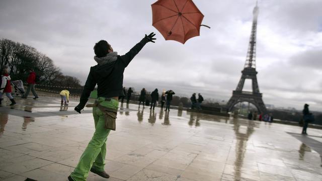 Un homme lâche son parapluie sur la place du Trocadero [Lionel Bonaventure / AFP/Archives]