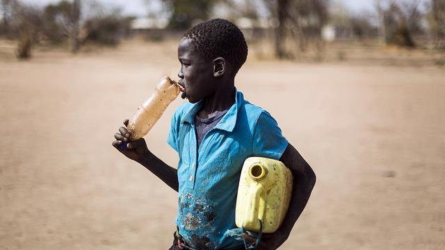 Un jeune garçon tient une bouteille de plastique et un jerrican, le 2 février 2013 dans un camp de personnes déplacées à JanJang au Soudan du Sud [Camille Lepage / AFP/Archives]