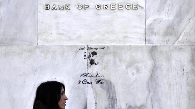 Une femme passe devant la Banque de Grèce, le 20 février 2013 à Athènes [Louisa Gouliamaki / AFP/Archives]