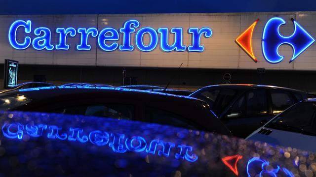 L'enseigne Carrefour se reflète sur les toits de voitures garées devant le supermarché de Quimper, le 13 février 2013 [Fred Tanneau / AFP/Archives]
