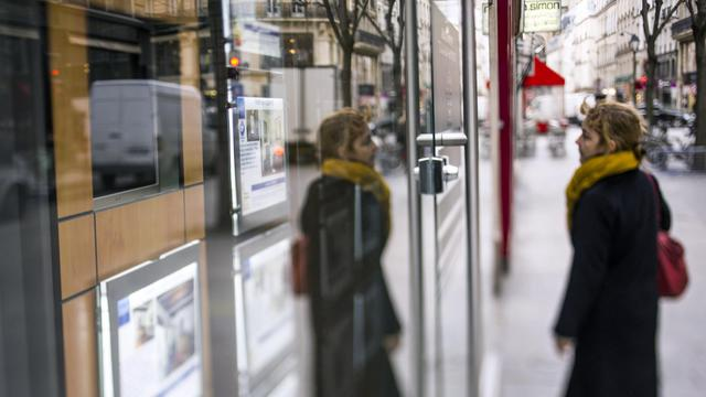 Une femme regarde des annonces immobilières [Fred Dufour / AFP/Archives]