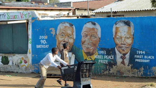Un enfant passe devant des portraits peints de Nelson Mandela à Soweto, le 29 mars 2013 [Alexander Joe / AFP/Archives]