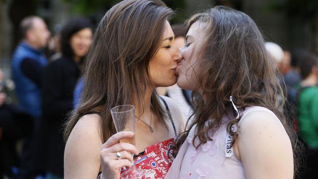 Deux jeunes filles s'embrassent à Paris, le 23 avril 2013, après le vote de la loi à l'Assemblée nationale [Kenzo Tribouillard / AFP/Archives]