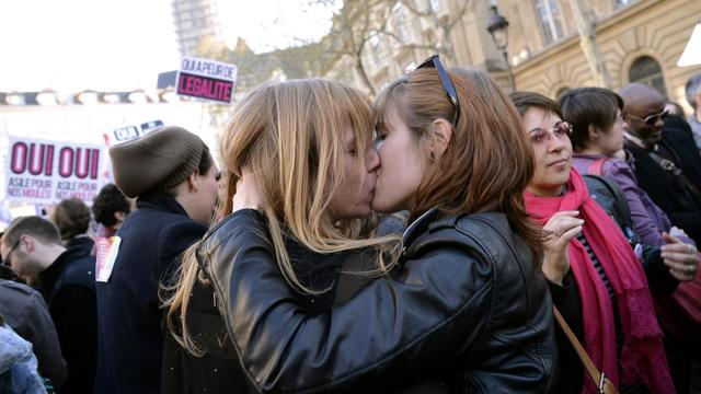 Deux femmes s'embrassent devant la mairie de Paris, le 23 avril 2013, après l'adoption par l'Assemblée nationale de la loi sur le mariage gay [Bertrand Guay / AFP/Archives]
