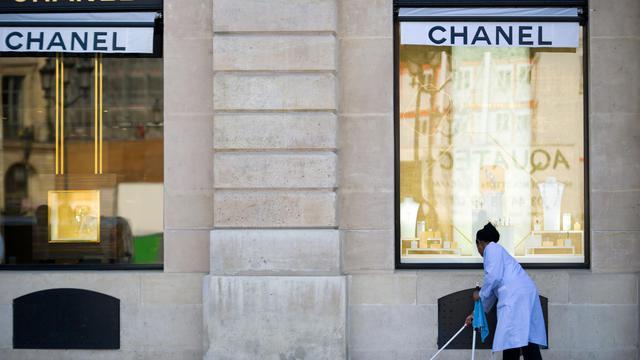 Une femme d'entretien nettoie le trottoir devant la boutique Chanel, place Vendôme à Paris, le 26 avril 2013 [Lionel Bonaventure / AFP/Archives]