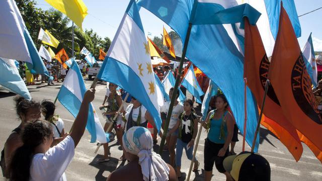 Des partisans de l'indépendantiste Oscar Temaru brandissent des drapeaux de son parti, le 5 mai 2013, jour du 2nd tour des élections territoriales en Polynésie française [Gregory Boissy / AFP/Archives]