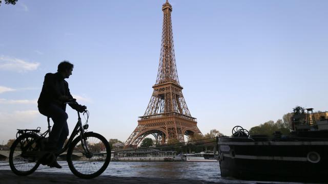 Un homme passe à bicyclette devant la Tour Eiffel, le 6 mai 2013 à Paris [Kenzo Tribouillard / AFP/Archives]
