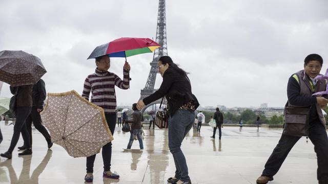 Des touristes avec leur parapluie devant la Tour Eiffel à Paris, le 20 mai 2013 [Fred Dufour / AFP]