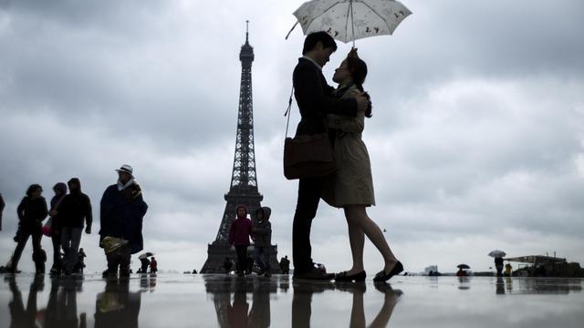 Un couple devant la Tour Eiffel, le 20 mai 2013 [Fred Dufour / AFP]